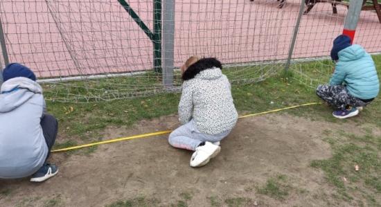 Na zdjęciu są dzieci w trakcie pomiaru boiska